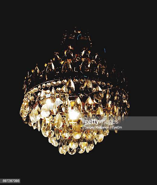 Low Angle View Of Illuminated Chandelier Against Black Background