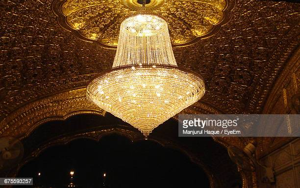 Low Angle View Of Illuminated Chandelier Hanging In Historic Church