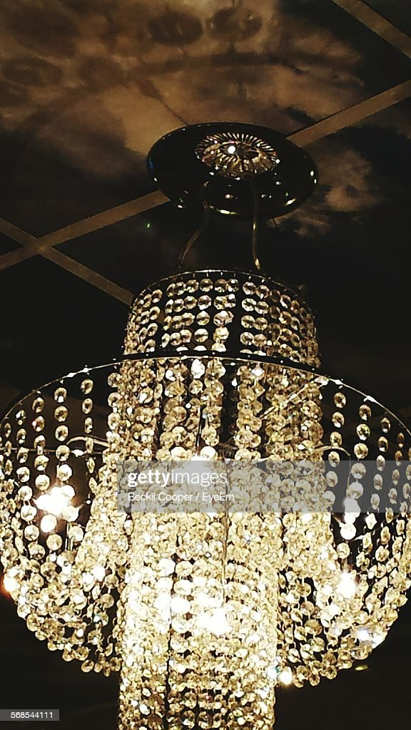 Low Angle View Of Illuminated Chandelier Hanging On Ceiling : Stock Photo