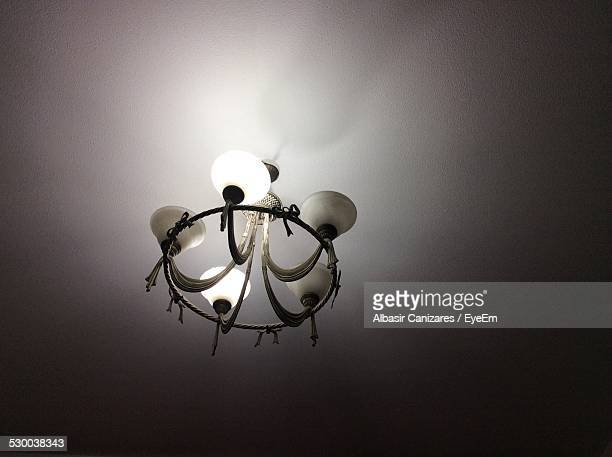 Low Angle View Of Illuminated Chandelier In Dark Room At Home