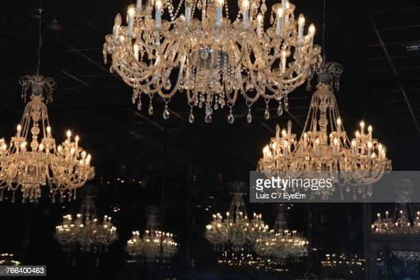 Low Angle View Of Illuminated Chandeliers Hanging On Ceiling In Darkroom