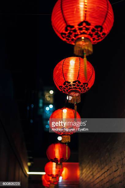 low angle view of illuminated chinese lanterns hanging at night - lantern festival stock photos and pictures