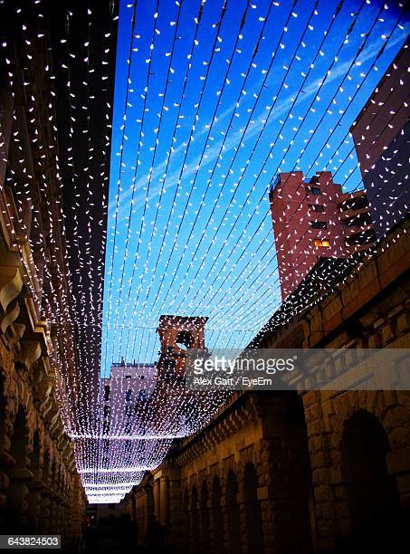 Low Angle View Of Illuminated Christmas Lights Decorations Amidst Buildings In City