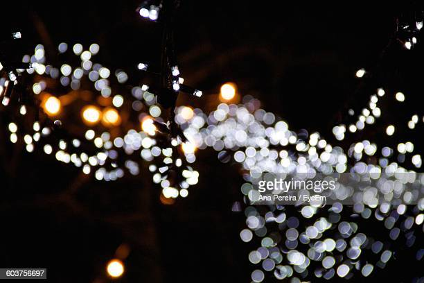 Low Angle View Of Illuminated Christmas Lights Glowing At Night