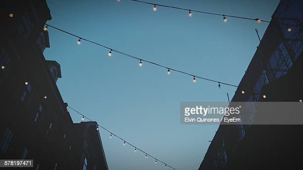 Low Angle View Of Illuminated Christmas Lights Hanging From Buildings Against Clear Sky