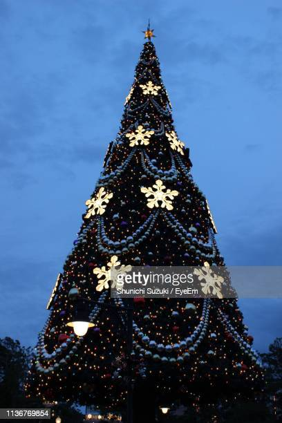 Low Angle View Of Illuminated Christmas Tree Against Blue Sky