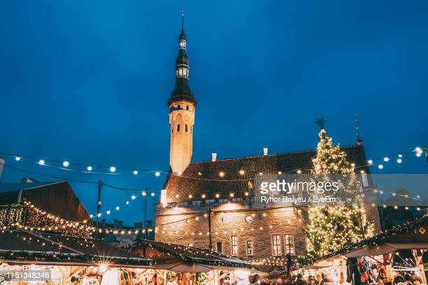 low angle view of illuminated church against sky at night during christmas - tallinn stock pictures, royalty-free photos & images