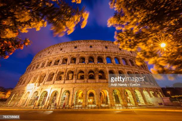 Low Angle View Of Illuminated Colosseum Against Sky At Dusk