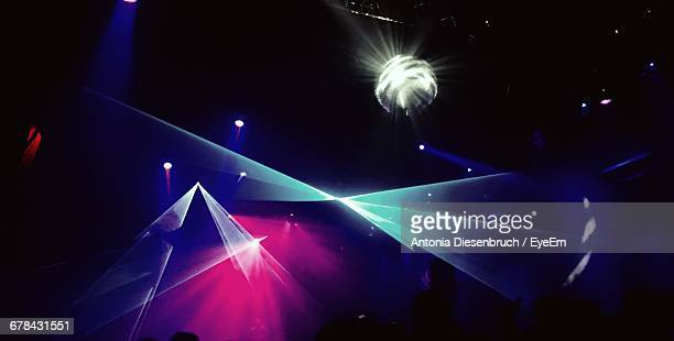 Low Angle View Of Illuminated Disco Ball And Light Beams In Nightclub