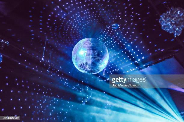 low angle view of illuminated disco ball at night - disco ball stock photos and pictures
