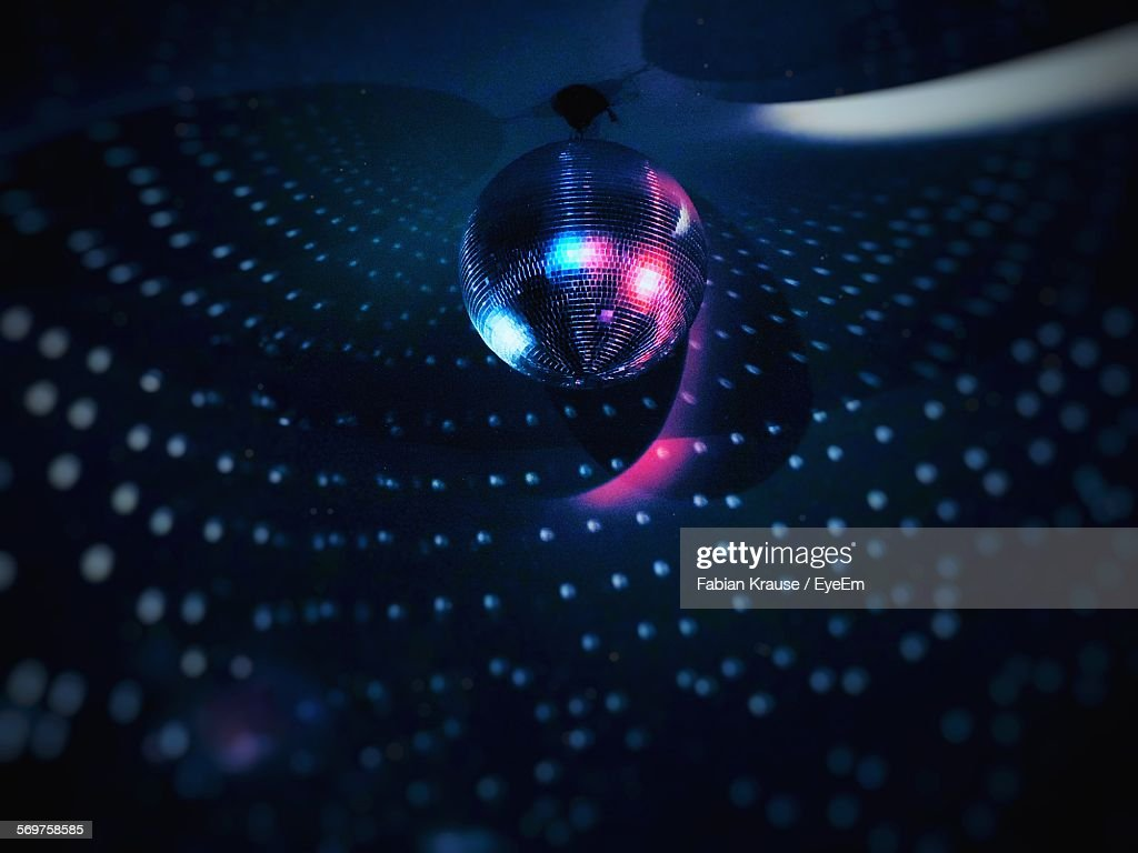 Low Angle View Of Illuminated Disco Ball Hanging From Ceiling : Stock Photo