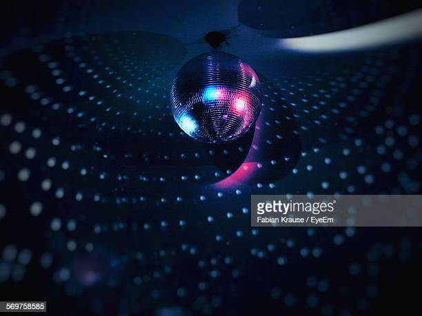 low angle view of illuminated disco ball hanging from ceiling - disco ball stock photos and pictures