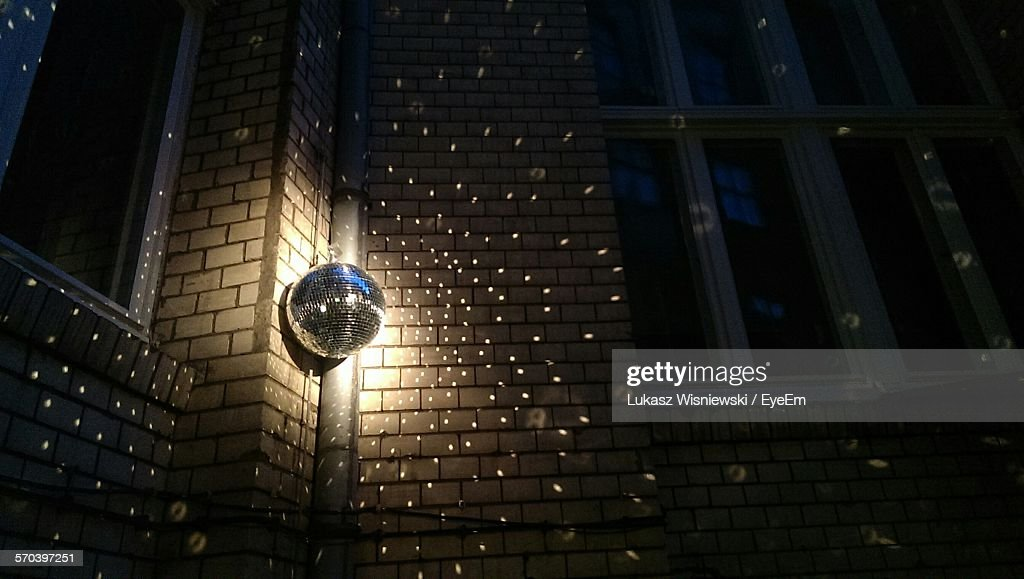 Low Angle View Of Illuminated Disco Ball Hanging On Wall : Stock Photo