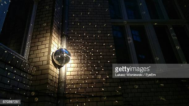 Low Angle View Of Illuminated Disco Ball Hanging On Wall