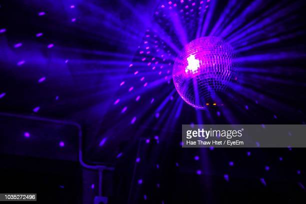 low angle view of illuminated disco ball in nightclub - disco ball fotografías e imágenes de stock