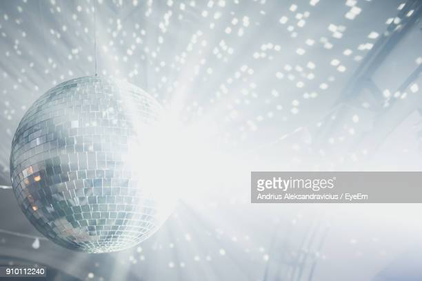 low angle view of illuminated disco ball - disco ball stock photos and pictures