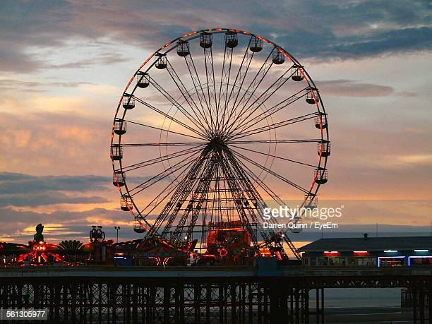 low angle view of illuminated ferris wheel against cloudy sky at dusk - blackpool stock pictures, royalty-free photos & images