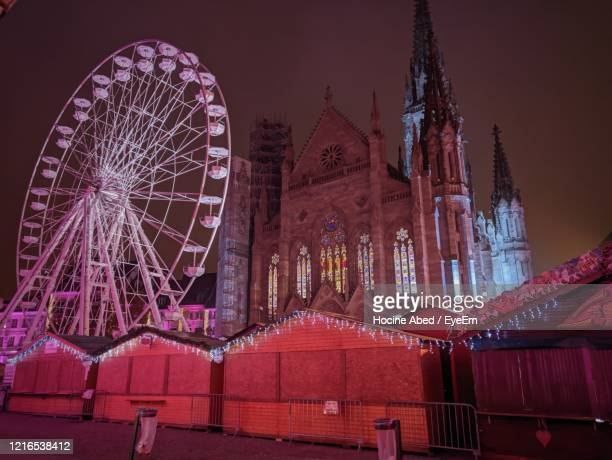 low angle view of illuminated ferris wheel against sky at night - mulhouse stock pictures, royalty-free photos & images