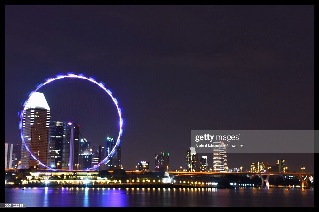 Low Angle View Of Illuminated Ferris Wheel Amidst Buildings By River Against Sky At Night