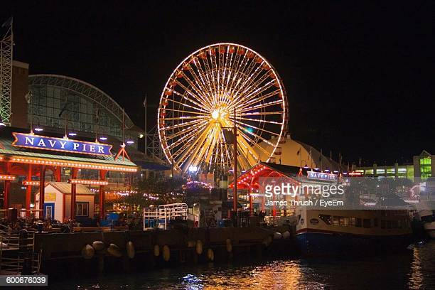 low angle view of illuminated ferris wheel at navy pier - navy pier stock pictures, royalty-free photos & images
