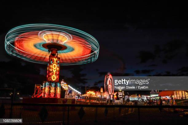 low angle view of illuminated ferris wheel in amusement park at night - traveling carnival stock pictures, royalty-free photos & images