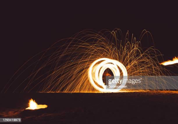 low angle view of illuminated fire against sky at night - bortes fotografías e imágenes de stock