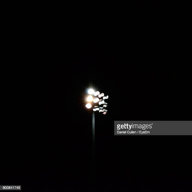 low angle view of illuminated floodlight against sky at night - stadium lights stock photos and pictures
