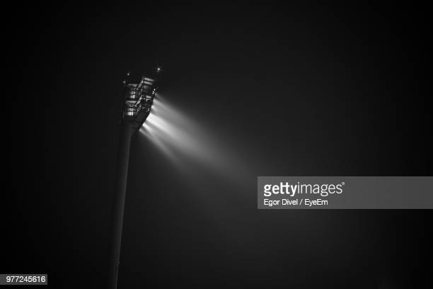 low angle view of illuminated floodlight against sky at night - stadium lights stock pictures, royalty-free photos & images