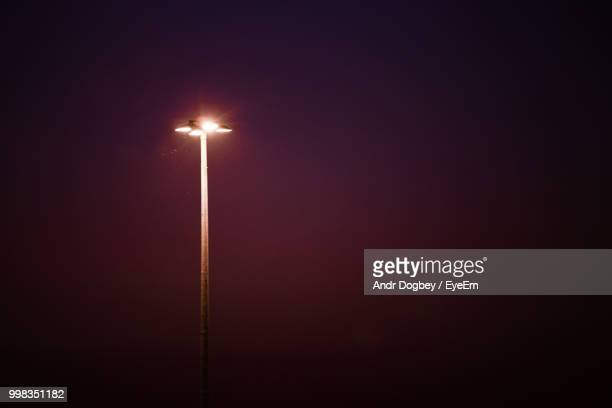 Low Angle View Of Illuminated Floodlight Against Sky At Night