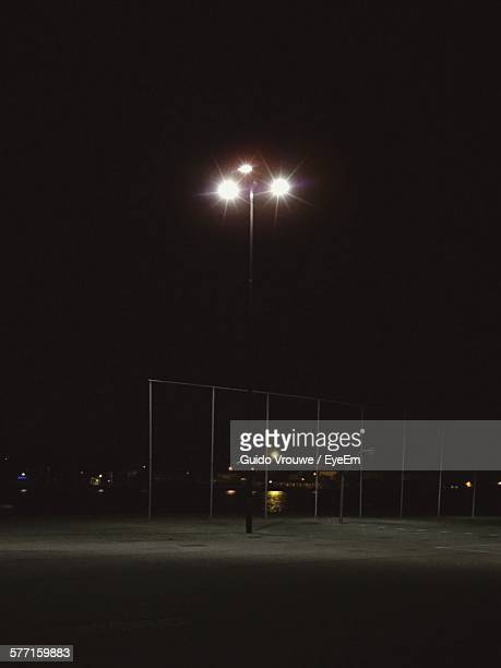 Low Angle View Of Illuminated Floodlight On Street Against Sky At Night