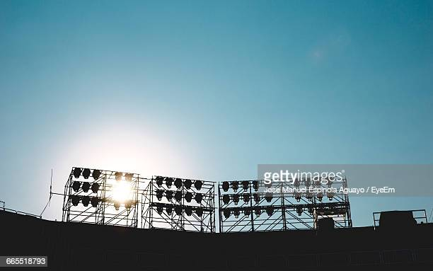 low angle view of illuminated floodlights on stadium against clear sky - stadium lights stock pictures, royalty-free photos & images