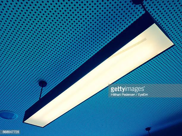 low angle view of illuminated fluorescent light hanging from blue ceiling - ceiling stock pictures, royalty-free photos & images