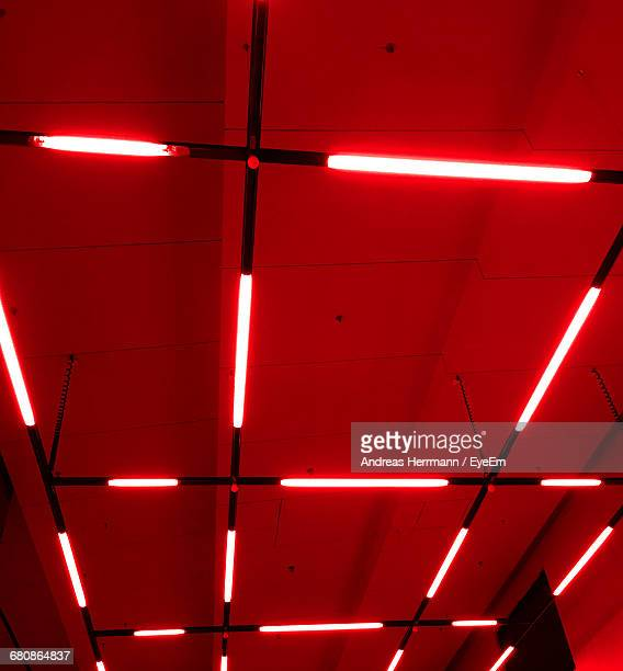 low angle view of illuminated fluorescent light on red ceiling - fluorescent light stock pictures, royalty-free photos & images