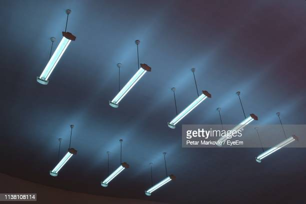 low angle view of illuminated fluorescent lights hanging from ceiling - ceiling stock pictures, royalty-free photos & images