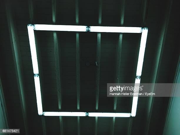 Low Angle View Of Illuminated Fluorescent Lights Mounted On Ceiling