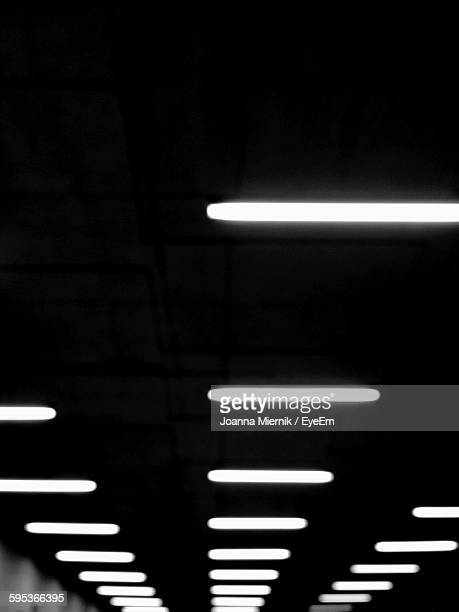 Low Angle View Of Illuminated Fluorescent Lights On Ceiling In Building