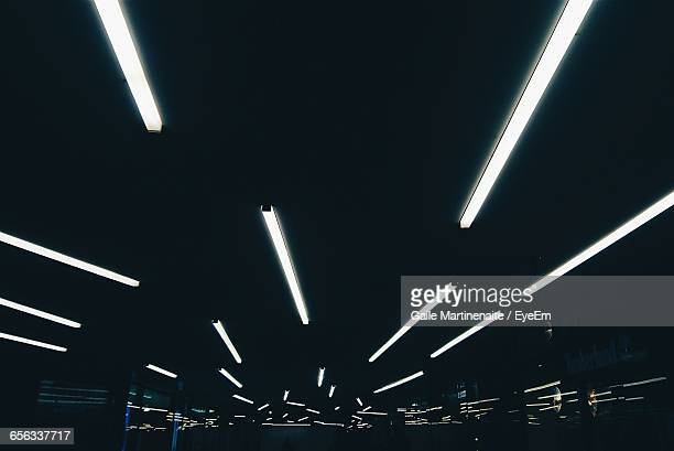 low angle view of illuminated fluorescent lights on ceiling in darkroom - fluorescent light stock pictures, royalty-free photos & images
