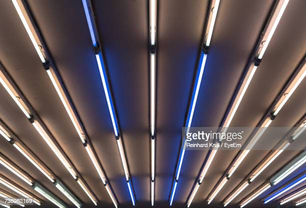 low angle view of illuminated fluorescent lights on ceiling - fluorescent light stock pictures, royalty-free photos & images