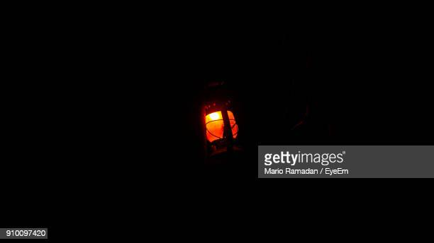 Low Angle View Of Illuminated Gas Lamp Against Black Background