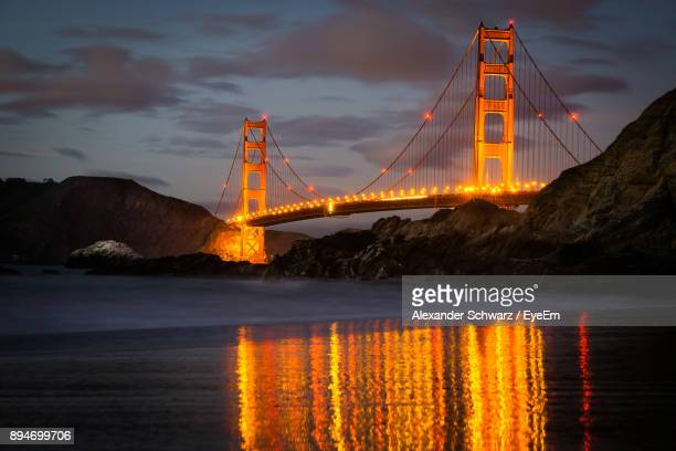 Low Angle View Of Illuminated Golden Gate Bridge Over Sea During Sunset
