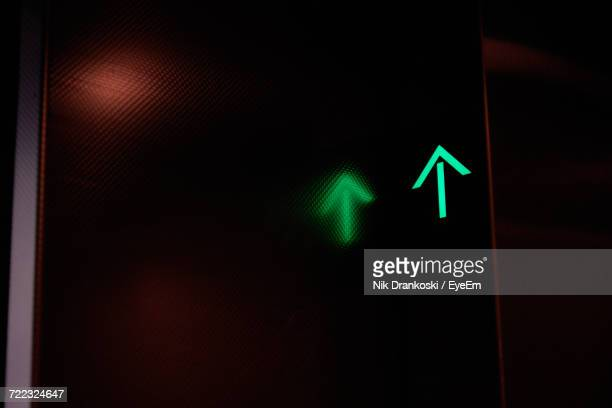Low Angle View Of Illuminated Green Arrow With Reflection In Dark Elevator