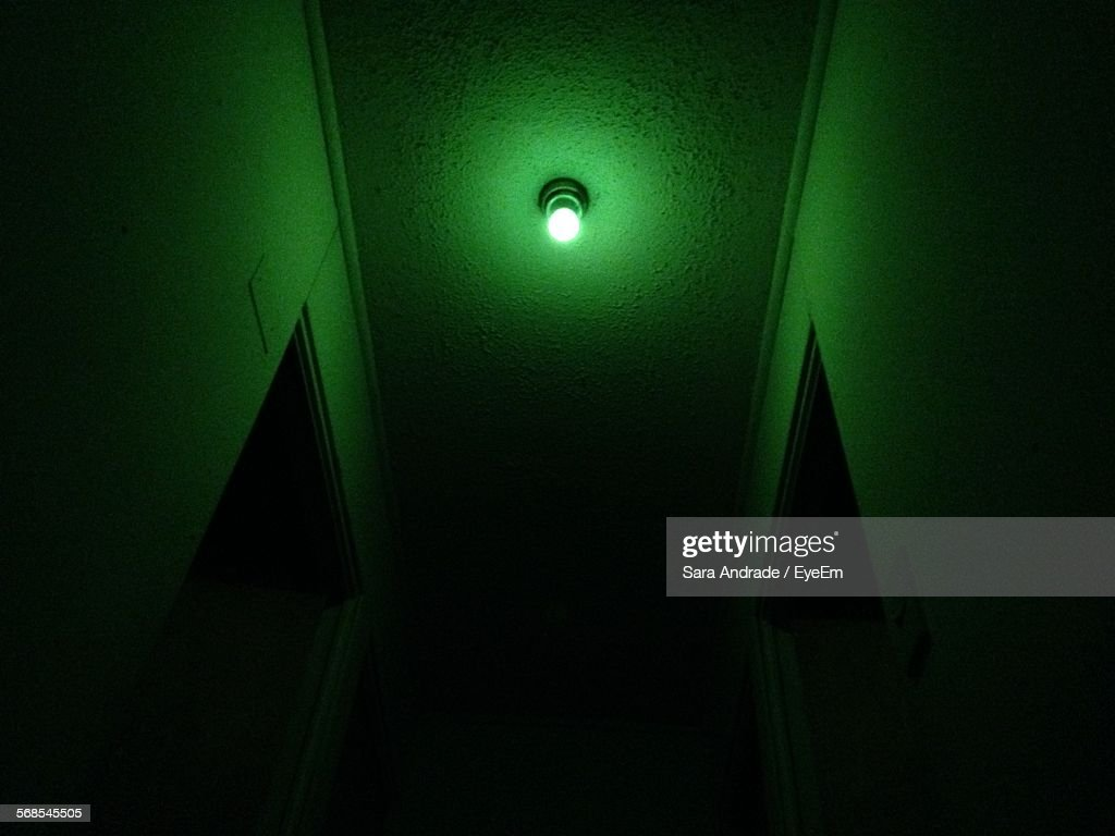 Low Angle View Of Illuminated Green Light On Ceiling : Stock Photo
