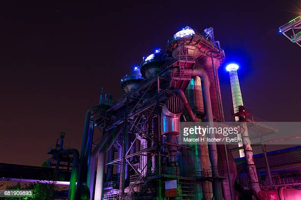 low angle view of illuminated industrial building at night - north rhine westphalia stock pictures, royalty-free photos & images