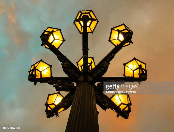 low angle view of illuminated lamps against cloudy sky during sunset - hopp stock-fotos und bilder