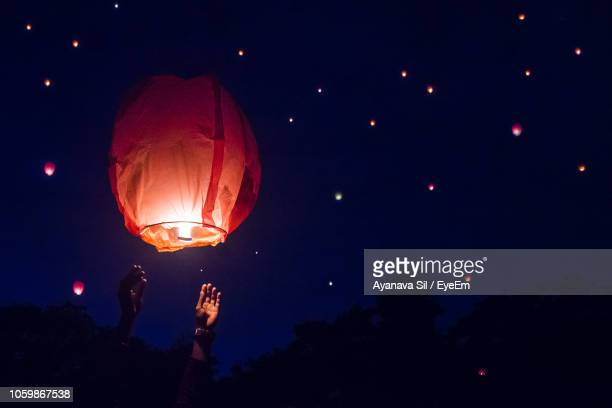 low angle view of illuminated lantern against sky at night - lantern stock photos and pictures