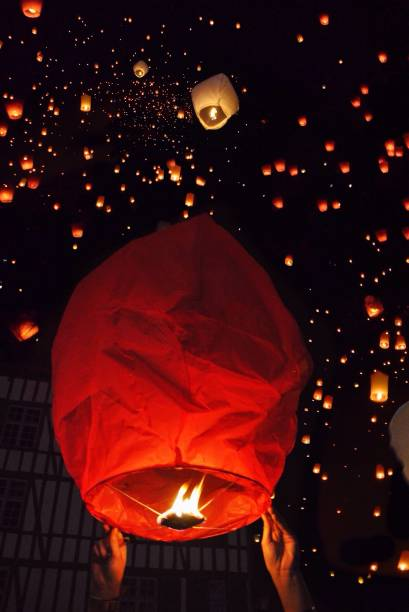Low Angle View Of Illuminated Lanterns Flying Against Sky At Night