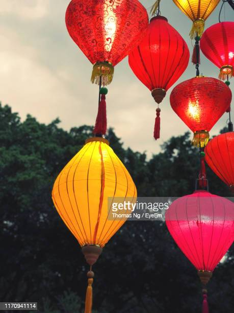 low angle view of illuminated lanterns hanging against sky - hanging stock pictures, royalty-free photos & images