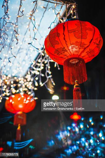 low angle view of illuminated lanterns hanging on roof at night - chinese lantern festival stock pictures, royalty-free photos & images