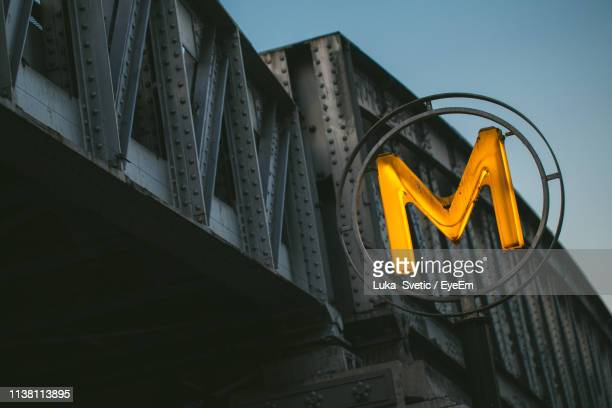 low angle view of illuminated letter m on bridge against sky - letter m stock pictures, royalty-free photos & images