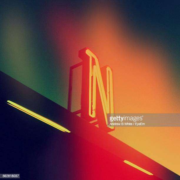 low angle view of illuminated letter n on building against sky - letter n stock pictures, royalty-free photos & images